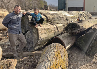 Brian and Mason Hearne with some of our reclaimed sinker redwood logs