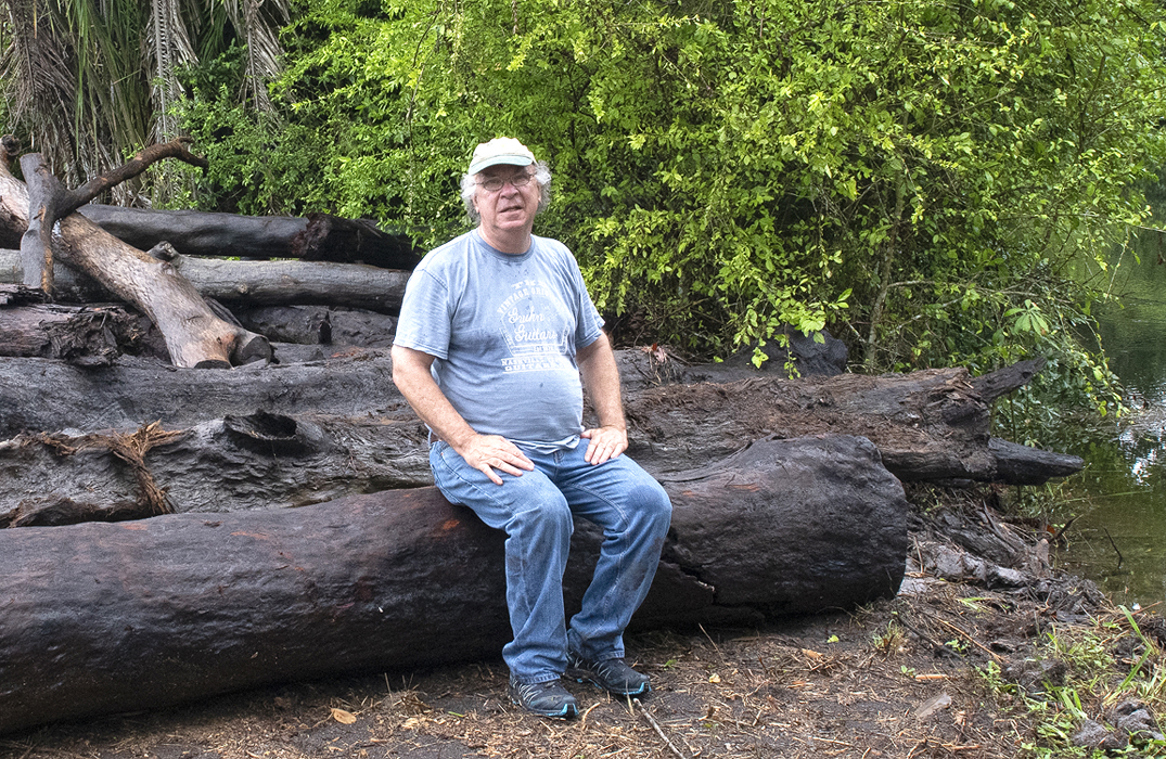 Rick Hearne sitting on a river salvaged Mahogany log